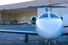 Private company jet outside hanger w planes stock photos