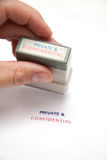 Private and confidential stamp. Hand using private and confidential stamp on white paper stock photo