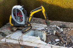 Private construction site. On a private swimming pool construction is dismantled by an excavator Royalty Free Stock Images