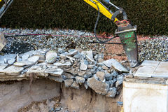 Private construction site. On a private swimming pool construction is dismantled by an excavator Stock Photos