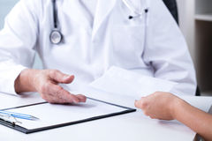 Private consultation. Senior male doctor and payment for private consultation Royalty Free Stock Images