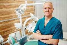 Private dentist. Confident cross-armed dentist in uniform looking at camera on background of medical equipment in his clinics Stock Image