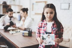 Private detective agency. Girl is posing with photo while man is showing clients photos on camera. Private detective agency. Girl in shirt is posing with photo stock photography