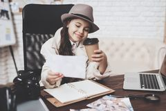 Private detective agency. Little girl is sitting at desk looking at different photos and drinking coffee. Private detective agency. Little girl in cloak and hat stock photos