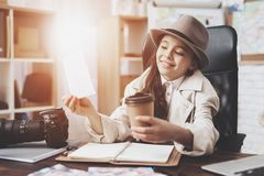 Private detective agency. Little girl is sitting at desk looking at different photos and drinking coffee. Private detective agency. Little girl in cloak and hat royalty free stock images