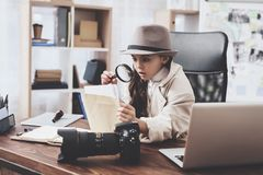 Private detective agency. Little girl is sitting at desk looking at photos with magnifying glass. Private detective agency. Little girl in cloak and hat is royalty free stock photography