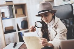 Private detective agency. Little girl is sitting at desk looking at photos with magnifying glass. Private detective agency. Little girl in cloak and hat is stock image