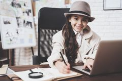 Private detective agency. Little girl is sitting at desk taking notes near laptop. Private detective agency. Little girl in cloak and hat is sitting at desk stock photo