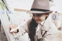Private detective agency. Little girl is drawing with marker on clues board. Private detective agency. Little girl in cloak and hat is drawing with marker on stock photo