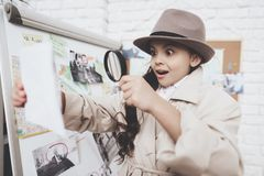 Private detective agency. Little girl is looking at photos near clues board. Private detective agency. Little girl in cloak and hat is looking at photos near stock photo