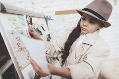 Private detective agency. Little girl is looking at photos near clues board. Private detective agency. Little girl in cloak and hat is looking at photos near stock images
