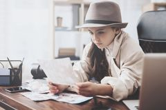 Private detective agency. Little girl is sitting at desk looking at different photos. Private detective agency. Little girl in cloak and hat is sitting at desk stock photos