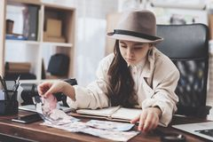 Private detective agency. Little girl is sitting at desk looking at different photos. Private detective agency. Little girl in cloak and hat is sitting at desk royalty free stock photo