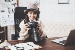 Private detective agency. Little girl is sitting at desk looking at photos in camera. Private detective agency. Little girl in cloak and hat is sitting at desk stock photo