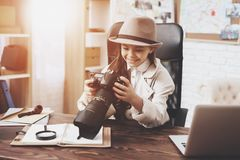 Private detective agency. Little girl is sitting at desk looking at photos in camera. Private detective agency. Little girl in cloak and hat is sitting at desk stock images