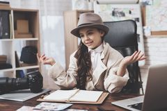 Private detective agency. Little girl is sitting at desk spreading out her hands. Private detective agency. Little girl in cloak and hat is sitting at desk royalty free stock photos
