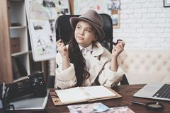 Private detective agency. Little girl is sitting at desk taking notes in notebook. stock images