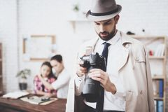 Private detective agency. Man is posing with camera, woman is holding her daughter. Private detective agency. Man in hat and cloak is posing with camera, women stock images