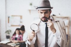 Private detective agency. Man is posing with magnifying glass, woman is holding her daughter. Private detective agency. Man in hat and cloak is posing with stock photo