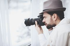 Private detective agency. Man is taking photos in window. Private detective agency. Man in hat is taking photos in window royalty free stock image