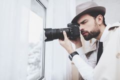 Private detective agency. Man is taking photos in window. Private detective agency. Man in hat is taking photos in window stock photography