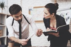 Private detective agency. Man is looking at clue, woman is taking notes in notebook. Private detective agency. Man with holster is looking at clue, women is royalty free stock photo