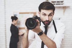 Private detective agency. Man is posing with camera, woman is looking at clues map. Private detective agency. Man with holster is posing with camera, women is royalty free stock photo