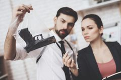 Private detective agency. Man and woman are looking at gun clue and taking notes. Private detective agency. Man with holster and women are looking at gun clue royalty free stock photography