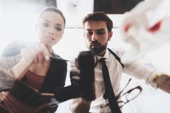 Private detective agency. Man and woman are looking at gun with magnifying glass. Private detective agency. Man with holster and women are looking at gun with royalty free stock photo