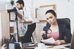 Private detective agency. Man is looking in camera, woman is looking at photo throuth magnifying glass. Private detective agency. Man with holsters is looking stock photos