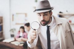 Private detective agency. Man is posing with magnifying glass, woman is holding her daughter. Private detective agency. Man in hat and cloak is posing with stock images
