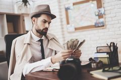 Private detective agency. Man is sitting at table counting money. Private detective agency. Man in hat and cloak is sitting at table counting money royalty free stock photos