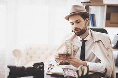 Private detective agency. Man is sitting at table counting money. Private detective agency. Man in hat and cloak is sitting at table counting money stock image