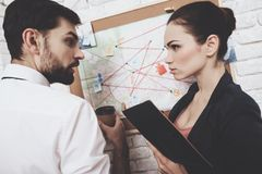 Private detective agency. Man and woman are looking at map, discussing clues. Private detective agency. Man in tie and women in jacket are looking at map royalty free stock photos