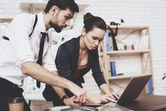Private detective agency. Man and woman are looking at clues on laptop. Private detective agency. Man with holster and women are looking at clues on laptop stock photos