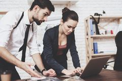 Private detective agency. Man and woman are looking at clues on laptop. Private detective agency. Man with holster and women are looking at clues on laptop royalty free stock photography
