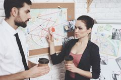 Private detective agency. Man and woman are looking at clues map, drinking coffee. royalty free stock photo