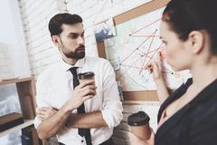 Private detective agency. Man and woman are looking at clues map, drinking coffee. Private detective agency. Man with tie and women in jacket are looking at royalty free stock photography