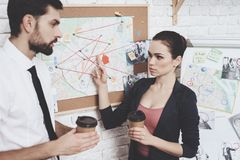 Private detective agency. Man and woman are looking at clues map, drinking coffee. Private detective agency. Man with tie and women in jacket are looking at royalty free stock images