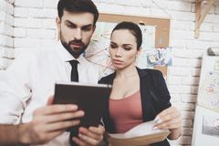 Private detective agency. Man and woman are looking at clues on tablet in office. Private detective agency. Man in tie and women in jacket are looking at clues stock images