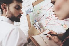 Private detective agency. Man and woman are looking at map, discussing clues. Private detective agency. Man in tie and women in jacket are looking at map royalty free stock images