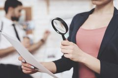 Private detective agency. Woman is posing with paper and magnifying glass, man is looking at clues map. Private detective agency. Woman in jacket is posing with royalty free stock photo
