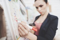 Private detective agency. Woman is putting photos marks with marker on clue map in office. Private detective agency. Woman in jacket is putting photos marks Stock Photo