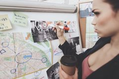 Private detective agency. Woman is putting photos marks with marker on clue map in office. Private detective agency. Woman in jacket is putting photos marks stock photos