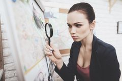 Private detective agency. Woman is looking at clue map with magnifying glass in office. Private detective agency. Woman in jacket is looking at clue map with royalty free stock photo