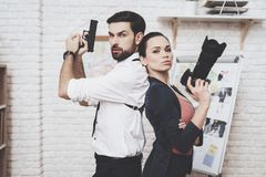 Private detective agency. Woman is posing with camera, man is posing with gun. Private detective agency. Woman is posing with camera, men with holster is posing royalty free stock image