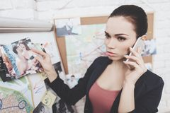 Private detective agency. Woman is putting photos on clue map in office. Private detective agency. Woman in jacket is putting photos on clue map in office royalty free stock image