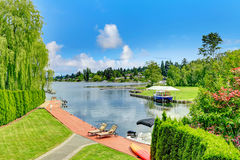 Private dock with deck chairs and boat. Royalty Free Stock Photo