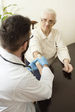 A private doctor`s office. Doctor examining an old woman`s hand. Old women at the doctor. The doctor provides the patient`s hand. Bandage the hand by a doctor Royalty Free Stock Images