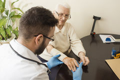 A private doctor`s office. Doctor examining an old woman`s hand. Old women at the doctor. The doctor provides the patient`s hand. Bandage the hand by a doctor Royalty Free Stock Photos